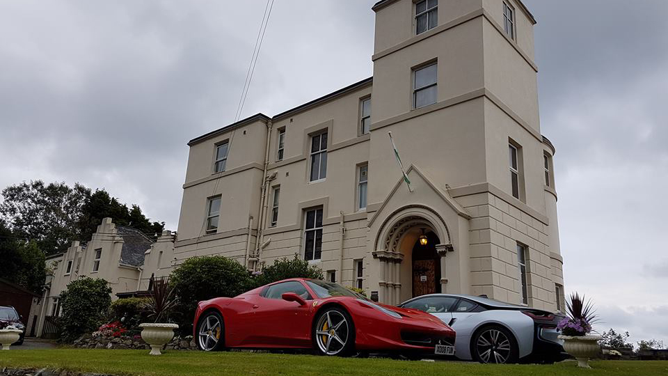 Two sports cars parked outside of Ty'r Graig Castle